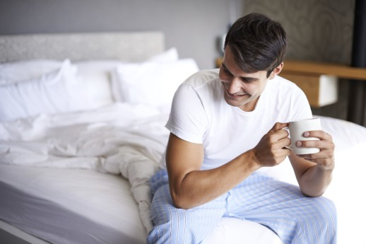 Cropped shot of a handsome young man drinking coffee on the edge of his bed